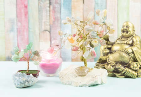 Zen background. Mental, body and soul balance, different spiritual objects Buddha figure, tree of happiness, money tree, candle, crystal cluster on table, painted colorful wooden background.