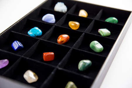 Variety of colorful semi precious stones crystals in organizer box sorted by color isolated on black.