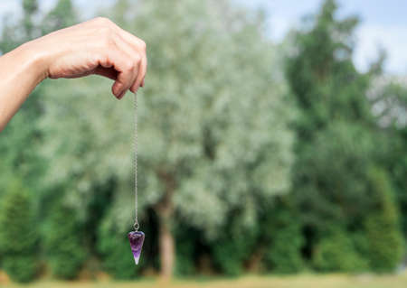 Woman hand holding and using purple Amethyst quartz crystal pendulum and using it, white background.
