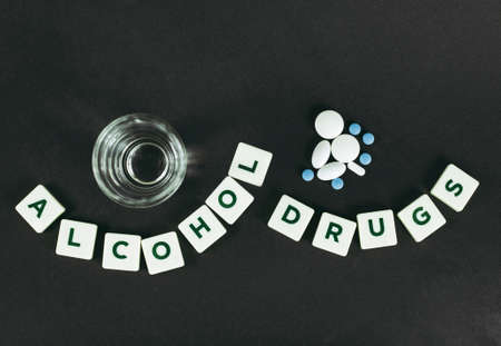 Drinking strong alcohol and taking drugs together could be dangerous concept, dark black background, flat lay view.