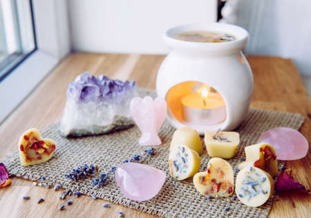 Homemade mini wax melts in aromatherapy lamp diffuser at home interior with rose quartz crystal hearts and angel for decoration on wooden window sill on winter. Seasonal spiritual zen concept. Zdjęcie Seryjne