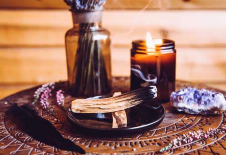 Palo Santo wood known as oily aromatic holy wood sticks smouldering on plate in home living room cleansing negative energy concept. Bohemian style cottage home decor.