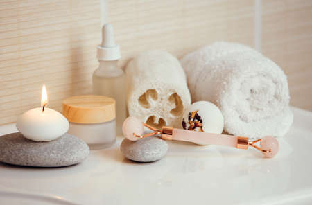 Home spa self care products in bathroom, facial massage rolling tool, moisturizing creams and oil, creamy bath bomb with dry rose petals. Modern orange filter look. Reklamní fotografie