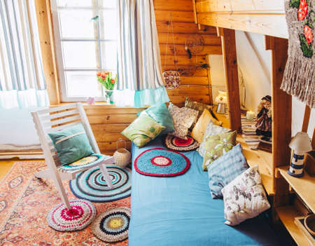 Maximalist maximalist home concept. Holiday home cabin bedroom with natural wooden board walls and ceiling and lot of different color details.