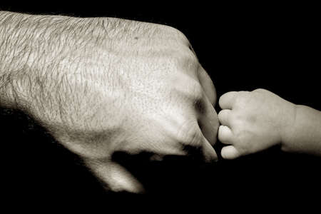 child protection: baby strong touching dad Stock Photo