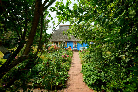 idyllic garden with blue thatched fisherman house Stock Photo