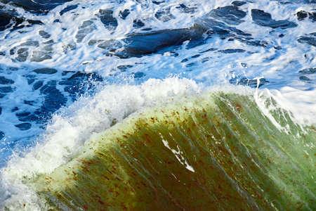 breaking wave in stormy blue green sea
