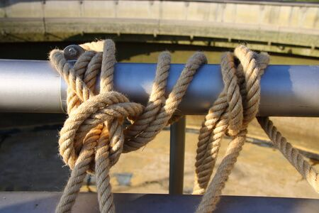 Thick ropes were attached to a pipe with knots Stock Photo