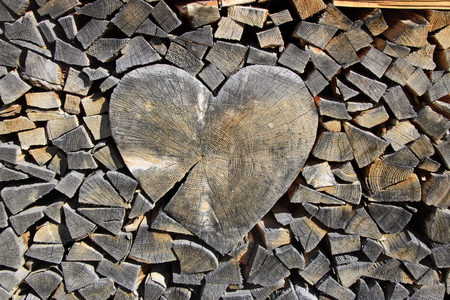 A heart of wood was embedded in a stack of split wood Banco de Imagens