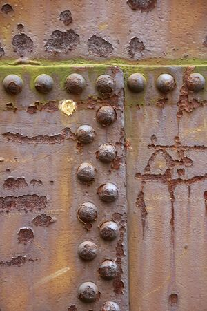 Old rivets in a steel wall that have the shape of the letter T Stock Photo
