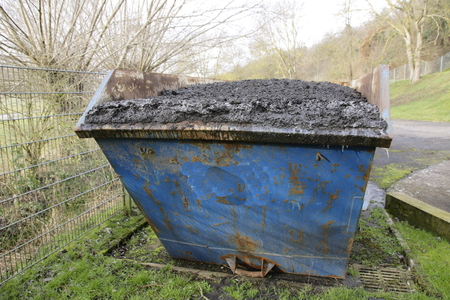 Waste container filled with sewage sludge. The container is overflowing, the mud could fall out in the back. Stock Photo