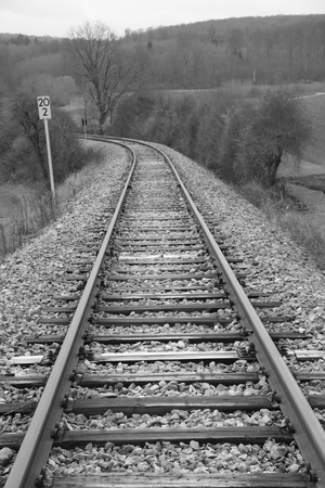 Railway tracks run away from the viewer in a curve. Imagens
