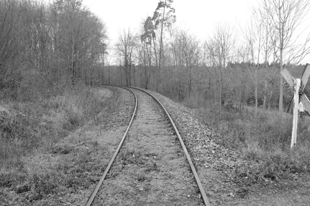 Railway tracks run straight away from the viewer. The picture was developed in black and white. Stockfoto - 117487897