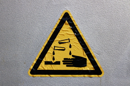 Yellow sticker with the symbol Caution Corrosive with black border