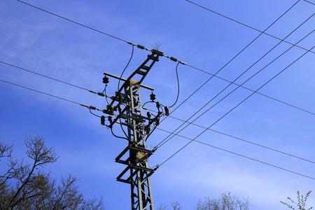 Poteau électrique et câble d'alimentation devant un ciel bleu