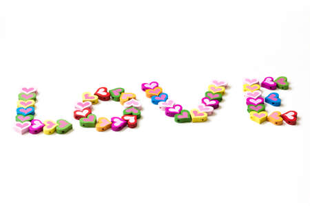 Word LOVE from the multicolored wood element in the shape of heart photo
