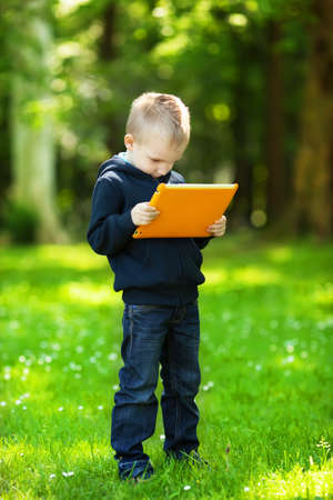Happy blond boy with tablet in park photo