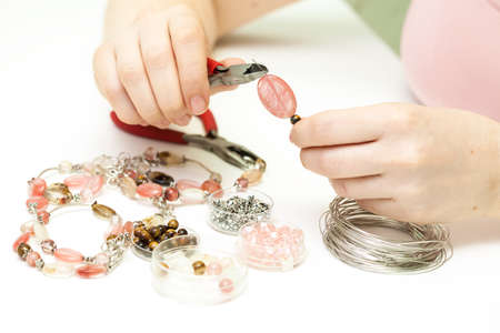 Woman making necklase from colorful plastic beads Imagens