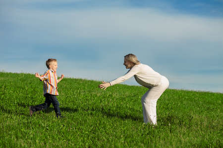 care giver: Beautiful boy and mom playing in spring park  Happy family concept
