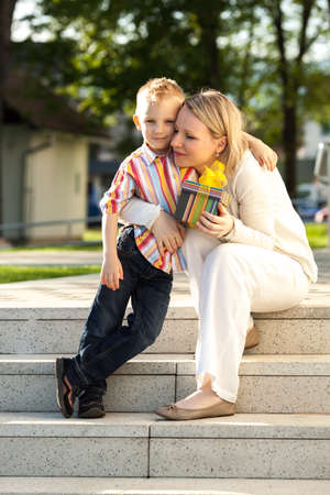 ��beautiful boy�: Beautiful boy and mom in spring park with present  Mothers day or birthday celebration concept