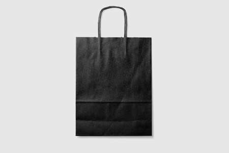 Mock up of a black paper shopping bag with handles on light gray background. High resolution.