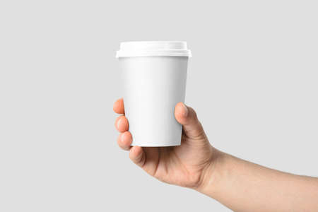 Mockup of male hand holding a Coffee paper cup isolated on light grey background. Reklamní fotografie - 143234661