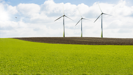 Wind turbines in landscape field against blue sky and clouds, alternative green energy Stock Photo