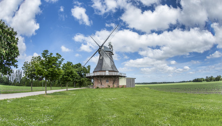 Old dutch windmill at landscape with trees and blue sky in background Archivio Fotografico - 97782039