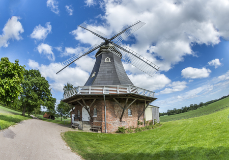 Old dutch windmill at landscape with trees and blue sky in background Archivio Fotografico - 97765046