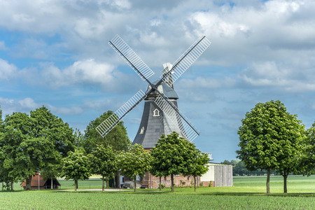 Old dutch windmill at landscape with trees and blue sky in background Archivio Fotografico - 97720224