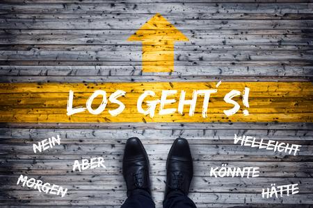 German Business Concept - Translation: Here We Go! - Black Shoes Standing At Starting Line