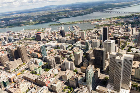 Aerial view of downtown Montreal and its skyscrapers looking south-east towards the old port and the St-Lawrence river on a sunny summer day. Quebec, Canada.