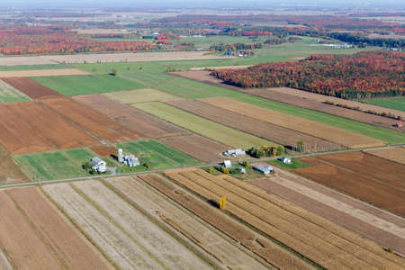 Aerial view of farms and farmfields at fall harvest season along a rural country road in Quebec, Canada. Imagens