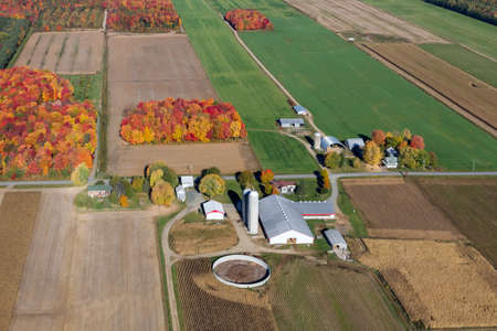 Autum aerial view of a farm and fields at harvest season in rural Quebec, Canada.