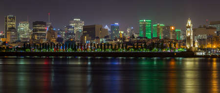 Panoramic skyline view on the Montreal skyline and the famed clock tower landmark along the Ste-Lawrence river at night time, Canada Imagens