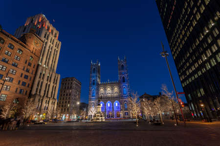 Autumn twilight scene in historical Old Montreal looking at the Maisonneuve monument and famed Notre Dame basilica. Canada.