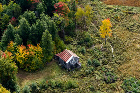 exclusive photo: Scenic aerial view of a cabin sitting in the middle of a colorful North American forest at fall