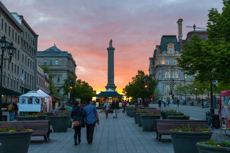 Old Montreal, May 30, 2015. Couples and tourists walking under the Sunset on historical Jacques Cartier square, Canada.