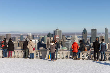 Montreal, March 8, 2015. Toruists and locals admiring the scenic view of the city skyline from the famed Mount-Royal on a sunny winter afternoon. Canada.