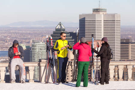 Montreal, March 8, 2015. Cross country skiers taking a break on the Mount-Royal belvedere to enjoy the skyline view on a sunny winter afternoon.