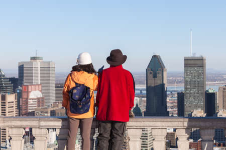 Montreal, March 8, 2015. A man and a woman admiring the panoramic skyline scene at the Mount Royal belvedere on a ssunny winter afternoon Montreal, Canada Editorial