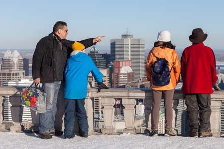 Montreal, March 8, 2015. A father showing his son the cityscape while a couple is admiring the panoramic skyline scene from the Mount Royal belvedere on a ssunny winter afternoon Montreal, Canada Editorial