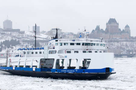 levis: Quebec city, January 21, 2017. The Alphonse Desjardins ferry crossing the partly frozen river from Quebec city and its historical landmark buildings and Levis on the south shore at dawn on a foggy winter day. Canada.