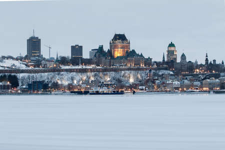 Quebec city, January 21, 2017. Skyline view of the historical city and landmark buildings standing along the frozen Ste-Lawrence river at dawn on a foggy winter day. Canada. Editorial