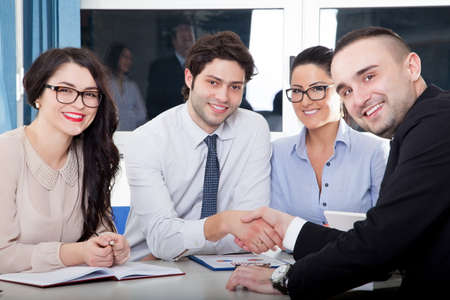 altogether: A business team of four plan work in office Stock Photo