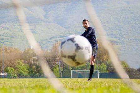 doing kick with ball on football stadium field