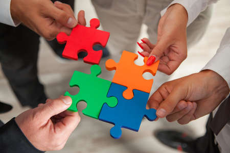 join the team: Group of business people assembling jigsaw puzzle and represent team support and help concept in office.