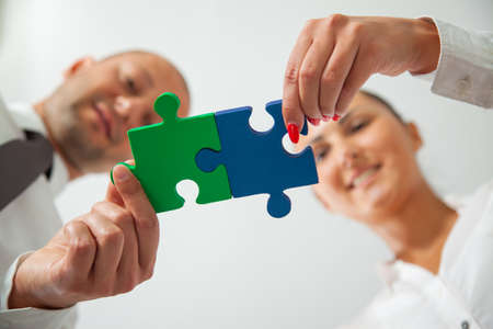 business connection: Teamwork - business people assembling jigsaw puzzle Stock Photo