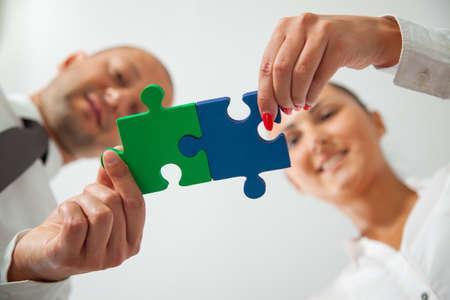 Teamwork - business people assembling jigsaw puzzle Standard-Bild