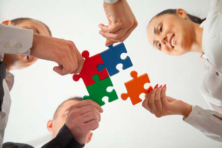 holding family together: Group of business people assembling jigsaw puzzle and represent team support and help concept in office.